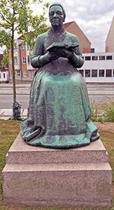 Gammel kone med bog fra 1959 bronze af billedhugger Ulf Rasmussen